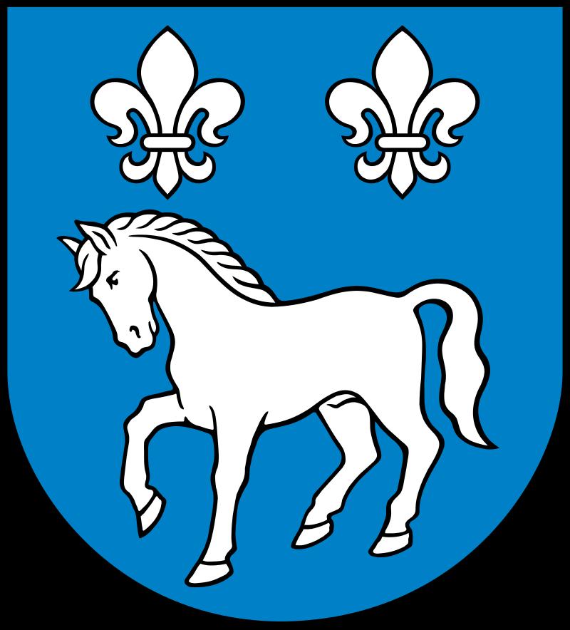 Na obrazku znajduje się herb Gminy Przykona. Herb gminy Przykona stanowi w polu błękitnym tarczy herbowej między dwiema liliami białymi (srebrnymi) u głowicy, koń kroczący biały (srebrny).