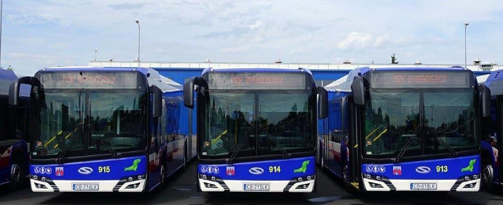 Na zdjęciu znajdują się trzy stojące obok siebie, frontem do fotografa, nowoczesne autobusy miejskie w barwach granatowo-białych.