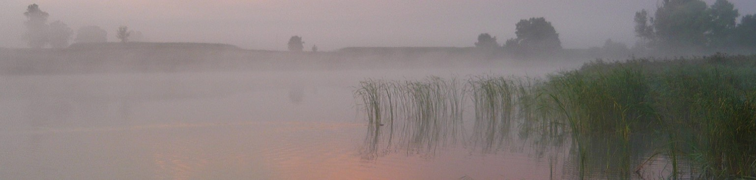 Zdjęcie przedstawia zachód słońca nad spowitym mgłą jeziorem.