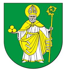 Herb przedstawia postać Św. Mikołaja z aureolą w stroju biskupim, ze złotym pastorałem  w lewej ręce i trzema złotymi kulami (bochnami chlebowymi) w prawej.