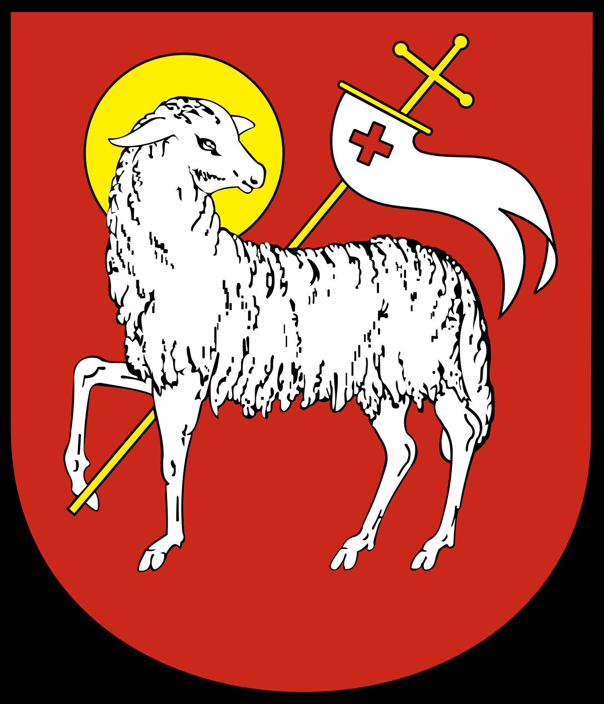 """herb przedstawia """"Wielkanocnego Baranka"""" na czerwonym polu, podtrzymującego przednią nogą proporczyk z wiszącą na nim białą flagą z krzyżem. Głowa baranka posiada żółtą (złotą) aureolę i skierowana jest w prawą stronę."""