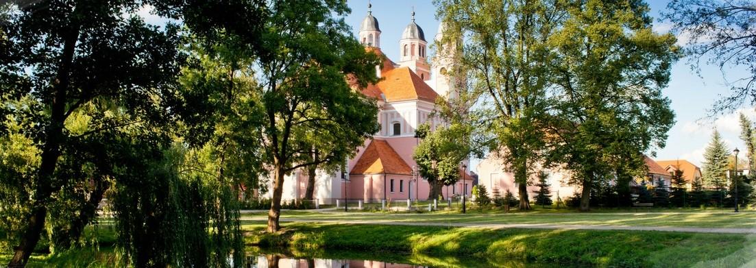 Zdjęcie przedstawia kościół otoczony zielenią i rzekę.
