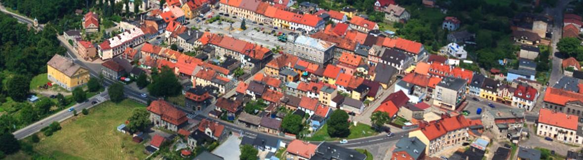 NA zdjęciu widać panoramę miejscowości z lotu ptaka. Rynek otoczony domostwami z przeważnie czerwonymi i pomarańczowymi dachami. Miejscowość przecina szosa. Skupisko domostw otacza letnia zieleń.