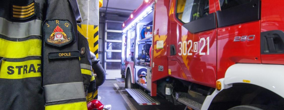 Na zdjęciu znajduje się uniform strażacki z wyszytą na ramieniu nazwą miasta Opole. Po prawej stronie widać czerwony wóz strażacki.
