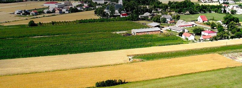 Zdjęcie przedstawia widok z lotu ptaka na miejscowość oraz okalające ją pola i łąki.