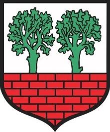 Herb Poddębic przedstawia w srebrnym polu czerwony mur miejski, zza którego wystają dwa zielone dęby.